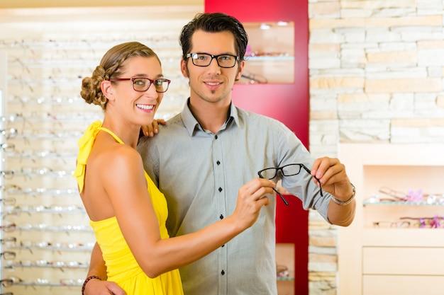 Jong koppel op opticien met een bril