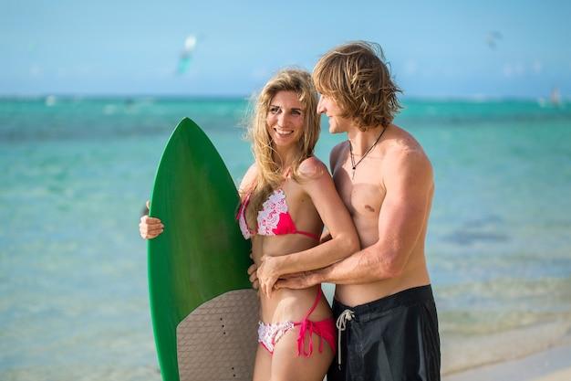 Jong koppel op strand met surfplank in de arm. surfen en outdoor sport levensstijl concept.