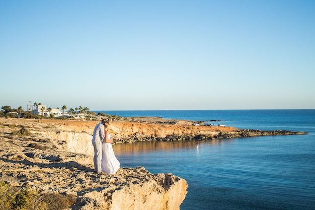 Jong koppel op strand zomervakantie, gelukkig lachend man en vrouw lopen kust zee oceaan vakantie reizen