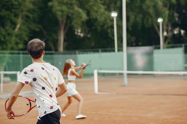 Jong koppel op tennisbaan. twee tennissers in een sportkleren.