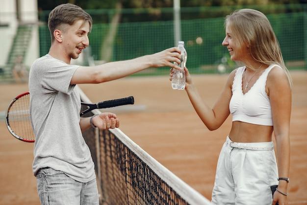 Jong koppel op tennisbaan. twee tennissers nemen een pauze.