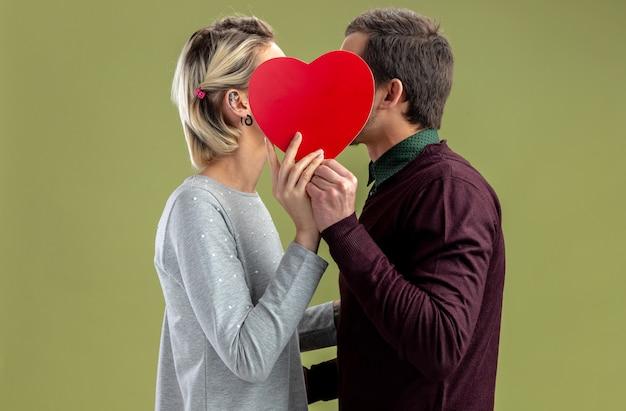 Jong koppel op valentijnsdag bedekt gezicht met hartvormige doos geïsoleerd op olijfgroene achtergrond