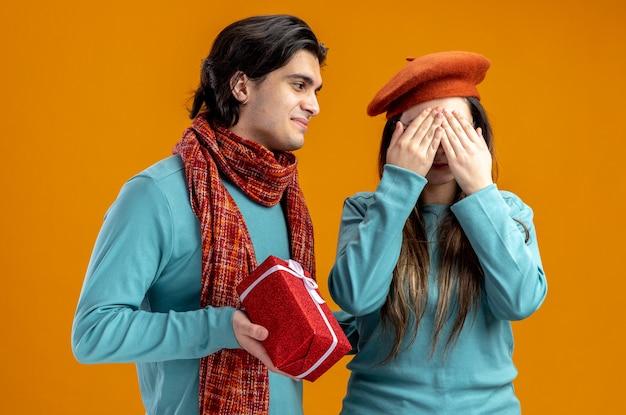 Jong koppel op valentijnsdag blij man geschenkdoos geven aan meisje geïsoleerd op oranje achtergrond