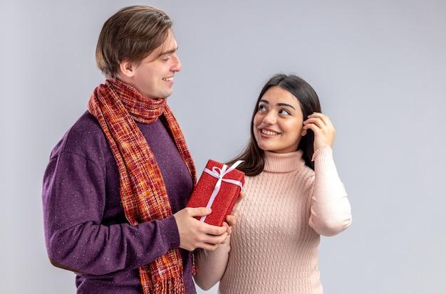 Jong koppel op valentijnsdag blij man geschenkdoos te geven aan lachende meisje kijken elkaar geïsoleerd op een witte achtergrond