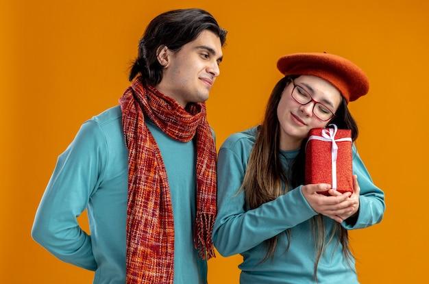 Jong koppel op valentijnsdag blij man met sjaal kijken naar meisje met geschenkdoos geïsoleerd op oranje achtergrond