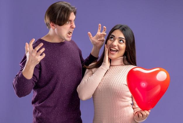 Jong koppel op valentijnsdag boze man kijken opgewonden meisje met hart ballon hand op wang geïsoleerd op blauwe achtergrond