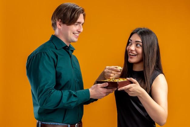 Jong koppel op valentijnsdag glimlachende man die doos snoepjes geeft aan lachend meisje dat naar elkaar kijkt geïsoleerd op oranje achtergrond orange