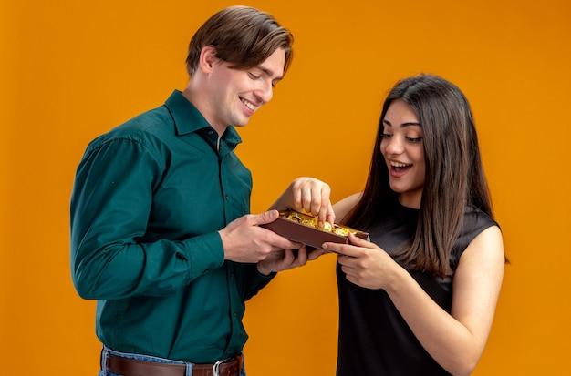 Jong koppel op valentijnsdag glimlachende man die doos snoepjes geeft aan verrast meisje geïsoleerd op oranje achtergrond