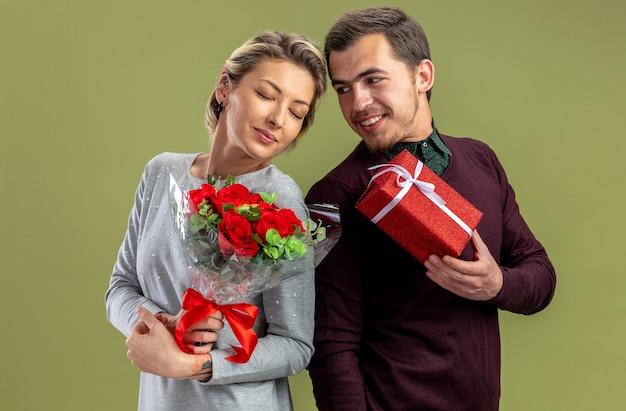 Jong koppel op valentijnsdag glimlachende man die geschenkdoos geeft aan blij meisje met boeket geïsoleerd op olijfgroene achtergrond