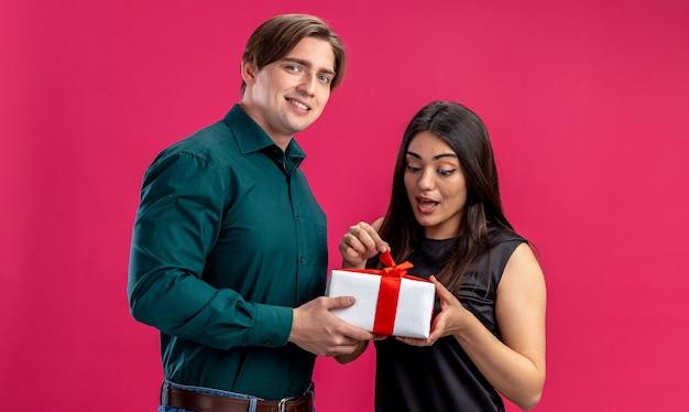 Jong koppel op valentijnsdag glimlachende man die geschenkdoos geeft aan verrast meisje geïsoleerd op roze achtergrond