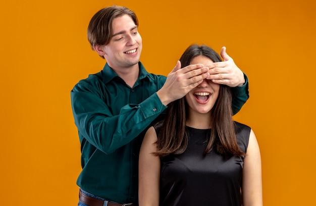 Jong koppel op valentijnsdag lachende man bedekt meisje ogen met handen geïsoleerd op oranje achtergrond