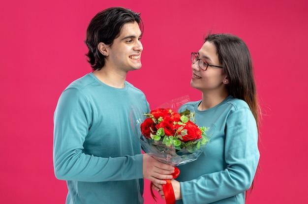 Jong koppel op valentijnsdag lachende man boeket geven aan blij meisje geïsoleerd op roze achtergrond