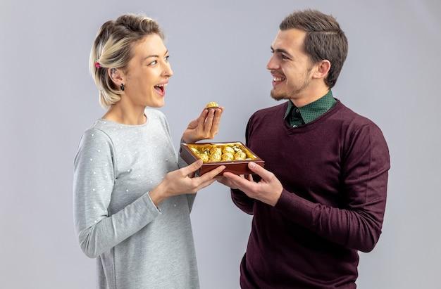 Jong koppel op valentijnsdag lachende man doos snoepjes geven aan lachende meisje geïsoleerd op een witte achtergrond