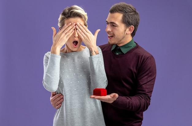 Jong koppel op valentijnsdag lachende man trouwring geven aan verrast meisje geïsoleerd op blauwe achtergrond