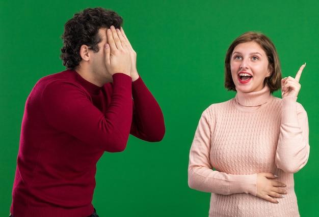Jong koppel op valentijnsdag man die gezicht bedekt met handen opgewonden vrouw die kijkt en omhoog wijst geïsoleerd op groene muur