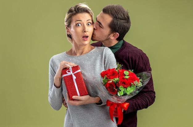 Jong koppel op valentijnsdag man met boeket zoenen verrast meisje met geschenkdoos geïsoleerd op olijfgroene achtergrond