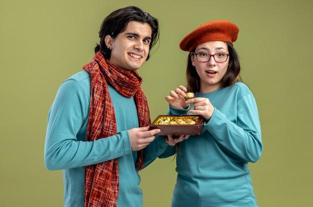 Jong koppel op valentijnsdag man met sjaal meisje met hoed glimlachende man die doos snoepjes geeft aan blij meisje geïsoleerd op olijfgroene achtergrond