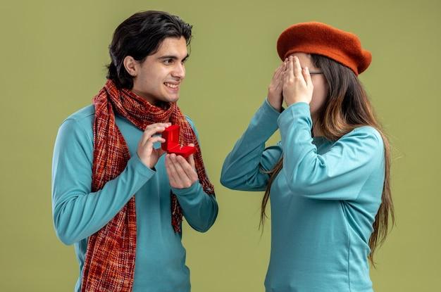 Jong koppel op valentijnsdag man met sjaal meisje met hoed glimlachende man die trouwring geeft aan meisje geïsoleerd op olijfgroene achtergrond