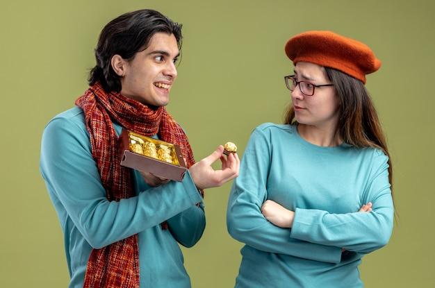 Jong koppel op valentijnsdag man met sjaal meisje met hoed lachende man geeft doos snoep geïsoleerd op olijf groene achtergrond