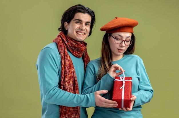 Jong koppel op valentijnsdag man met sjaal meisje met hoed meisje met geschenkdoos geïsoleerd op olijfgroene achtergrond
