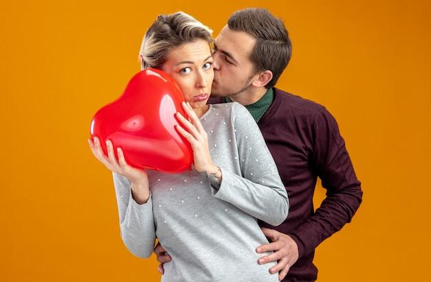Jong koppel op valentijnsdag man zoenen meisje met ballon geïsoleerd op oranje background