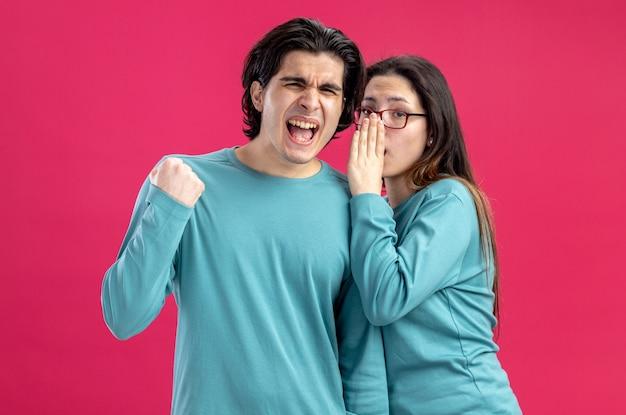 Jong koppel op valentijnsdag meisje fluistert man met ja gebaar geïsoleerd op roze achtergrond