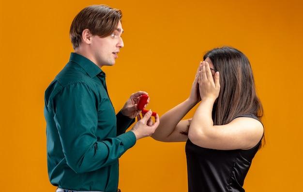 Jong koppel op valentijnsdag onder de indruk man trouwring geven aan meisje bedekte ogen met hand geïsoleerd op oranje achtergrond