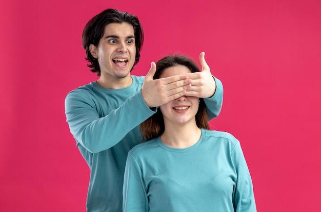 Jong koppel op valentijnsdag opgewonden man bedekt meisjes ogen met handen geïsoleerd op roze achtergrond