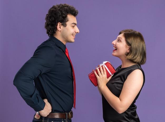 Jong koppel op valentijnsdag staande in profiel bekijken lachende man houden handen op taille opgewonden vrouw met cadeaupakket kijken elkaar geïsoleerd op paarse muur