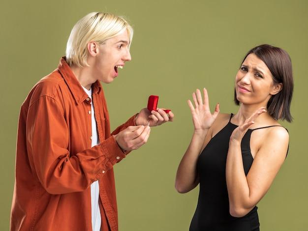 Jong koppel op valentijnsdag staande in profiel weergave opgewonden man verlovingsring geven aan vrouw en fronsen vrouw met lege handen geïsoleerd op olijf groene muur