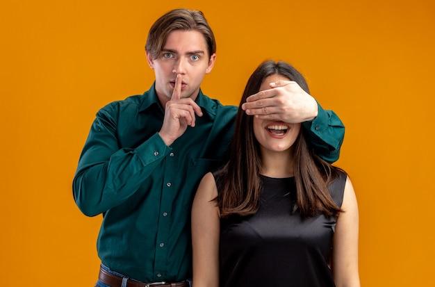 Jong koppel op valentijnsdag strikte man bedekt meisje ogen met hand tonen stilte gebaar geïsoleerd op oranje achtergrond