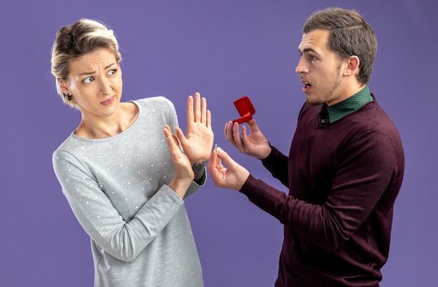 Jong koppel op valentijnsdag verwarde man trouwring geven aan ontevreden meisje geïsoleerd op blauwe achtergrond