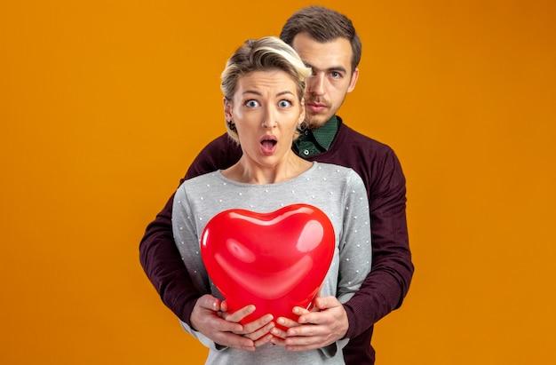 Jong koppel op valentijnsdag zelfverzekerde man die achter een verrast meisje staat met een hartballon geïsoleerd op een oranje achtergrond