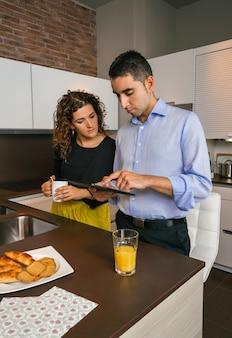 Jong koppel op zoek naar nieuws in elektronische tablet terwijl ze thuis snelle koffie drinken voordat ze naar hun werk gaan