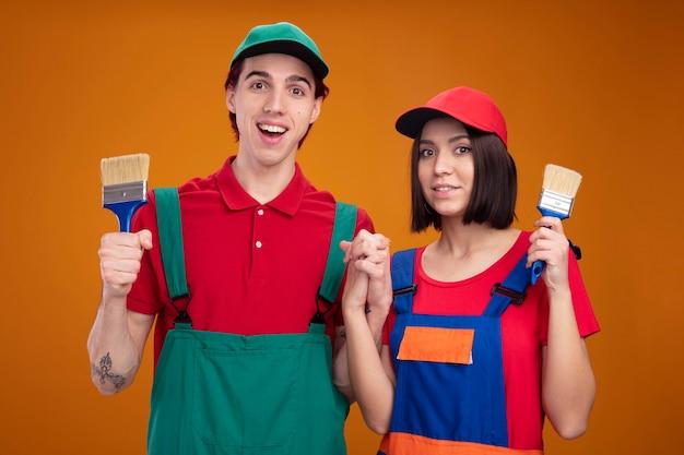 Jong koppel opgewonden man blij meisje in bouwvakker uniform en pet hand in hand met kwast in hun handen