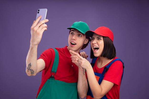 Jong koppel opgewonden man en vrolijk meisje in bouwvakkeruniform en pet-man die mobiele telefoon opheft, zowel kijkend als ernaar wijzend