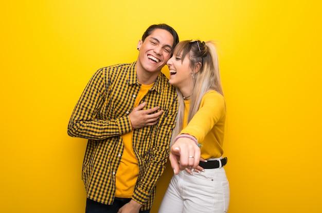 Jong koppel over levendige gele achtergrond wijzen met de vinger naar iemand