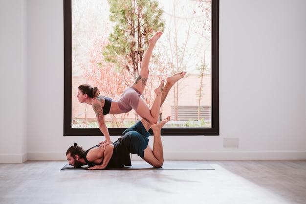 Jong koppel paar beoefenen van acro yoga bij het raam in de studio of sportschool. gezonde levensstijl