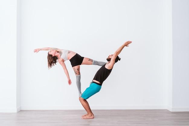 Jong koppel paar beoefenen van acro yoga in witte studio of sportschool. gezonde levensstijl