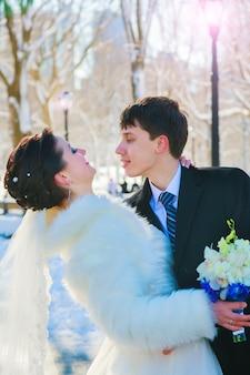 Jong koppel pasgetrouwden wandelen in een winter forest in de sneeuw. bruid en bruidegom knuffelen in het park in de winter. mooie man en vrouw in hun trouwkleding behoren tot de dennen.