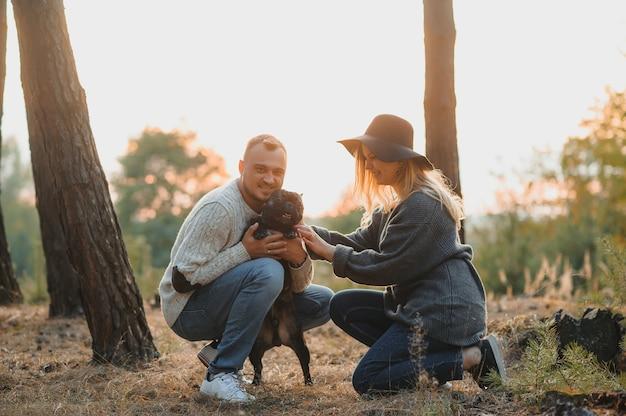 Jong koppel plezier met hun hond haski bij zonsondergang buiten de stad in de natuur