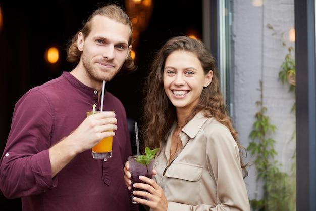 Jong koppel poseren buitenshuis door cafe