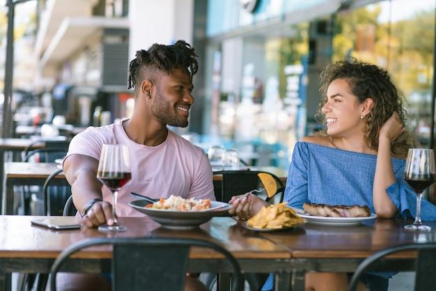 Jong koppel praten en genieten tijdens de lunch samen in een restaurant.