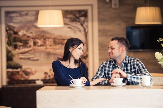 Jong koppel praten in koffie winkel