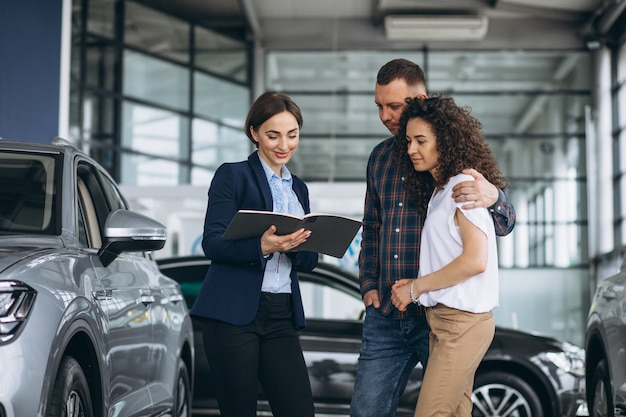 Jong koppel praten met een verkoper in een autotoonzaal
