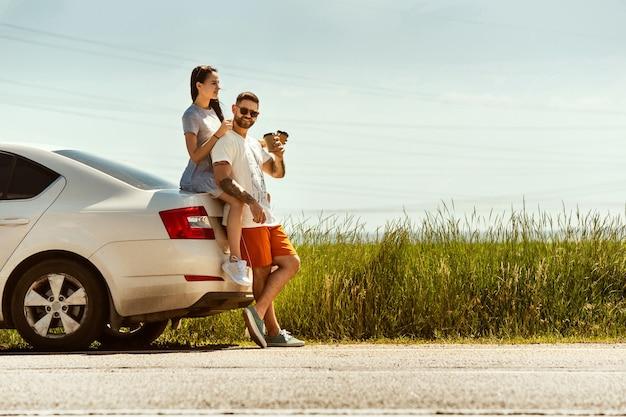 Jong koppel reizen op de auto in zonnige dag