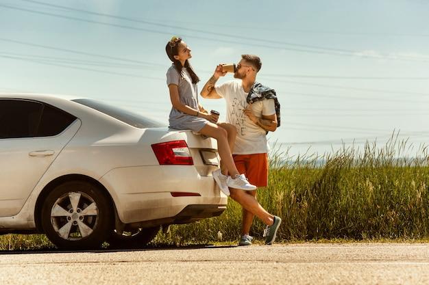 Jong koppel reizen op de auto in zonnige dag Gratis Foto