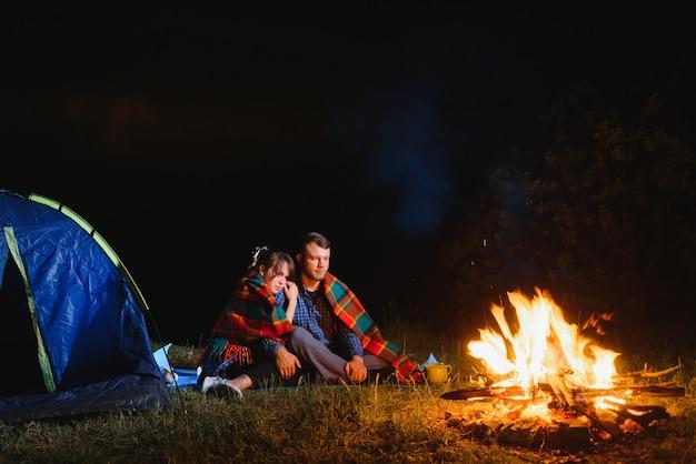 Jong koppel rust bij vreugdevuur naast kamp en blauwe toeristische tent, thee drinken, genieten van de nachtelijke hemel