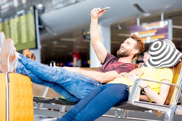 Jong koppel rustend op de stoelen in de wachtkamer van de luchthaven. lang wachten op het vliegtuig