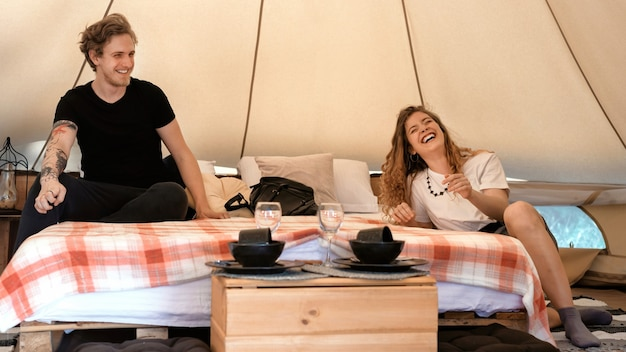 Jong koppel rustend op het bed in de tent bij glamping glimlachen en lachen
